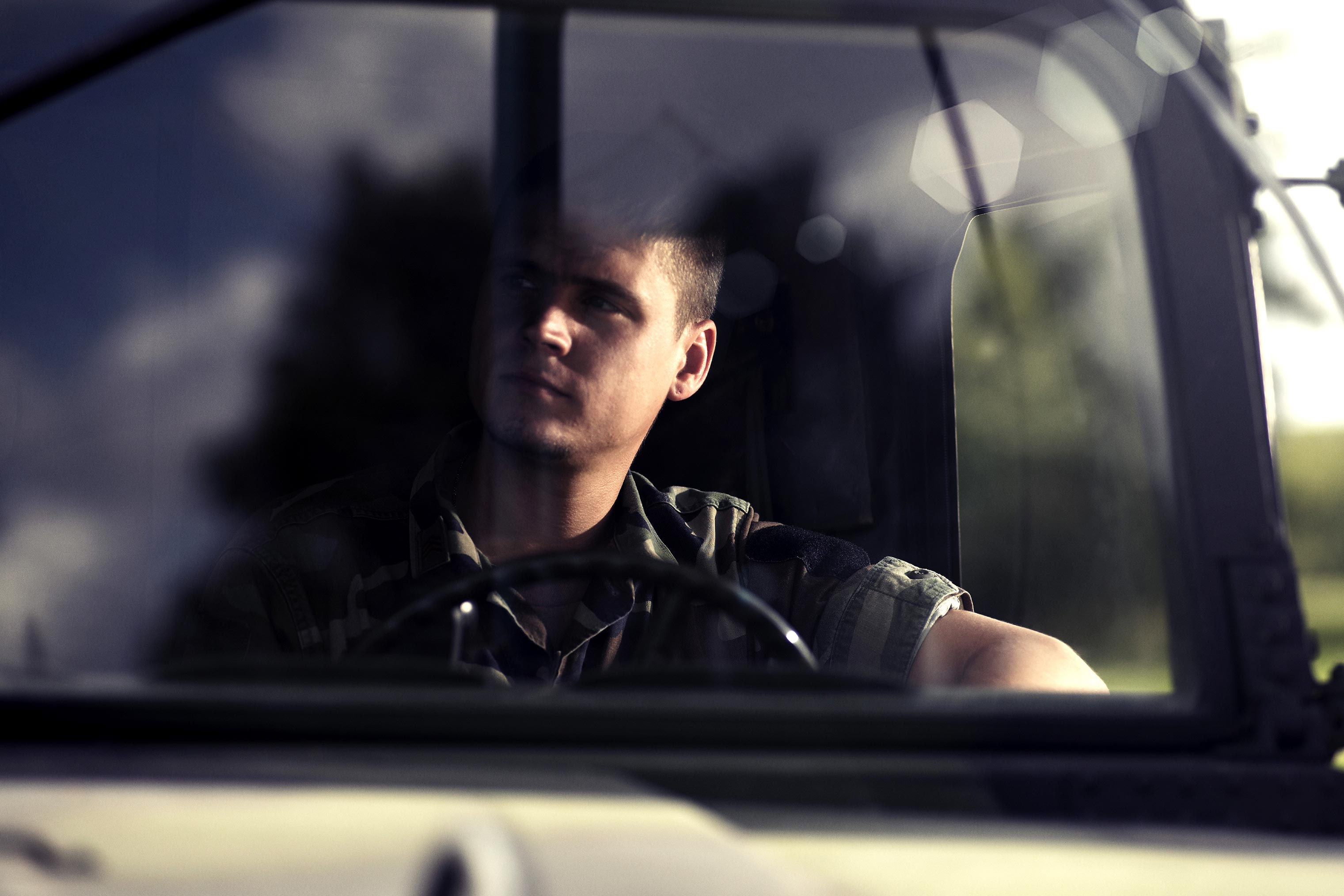 Soldier behind windscreen of red cross army ambulance.