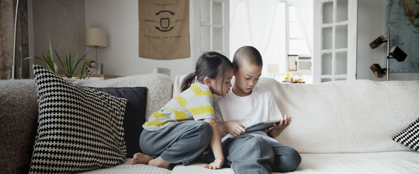 Children on couch with tablet